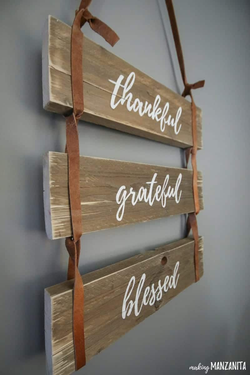 Side view of hanging leather sign with painted words that says thankful grateful blessed hanging on wall with gray paint