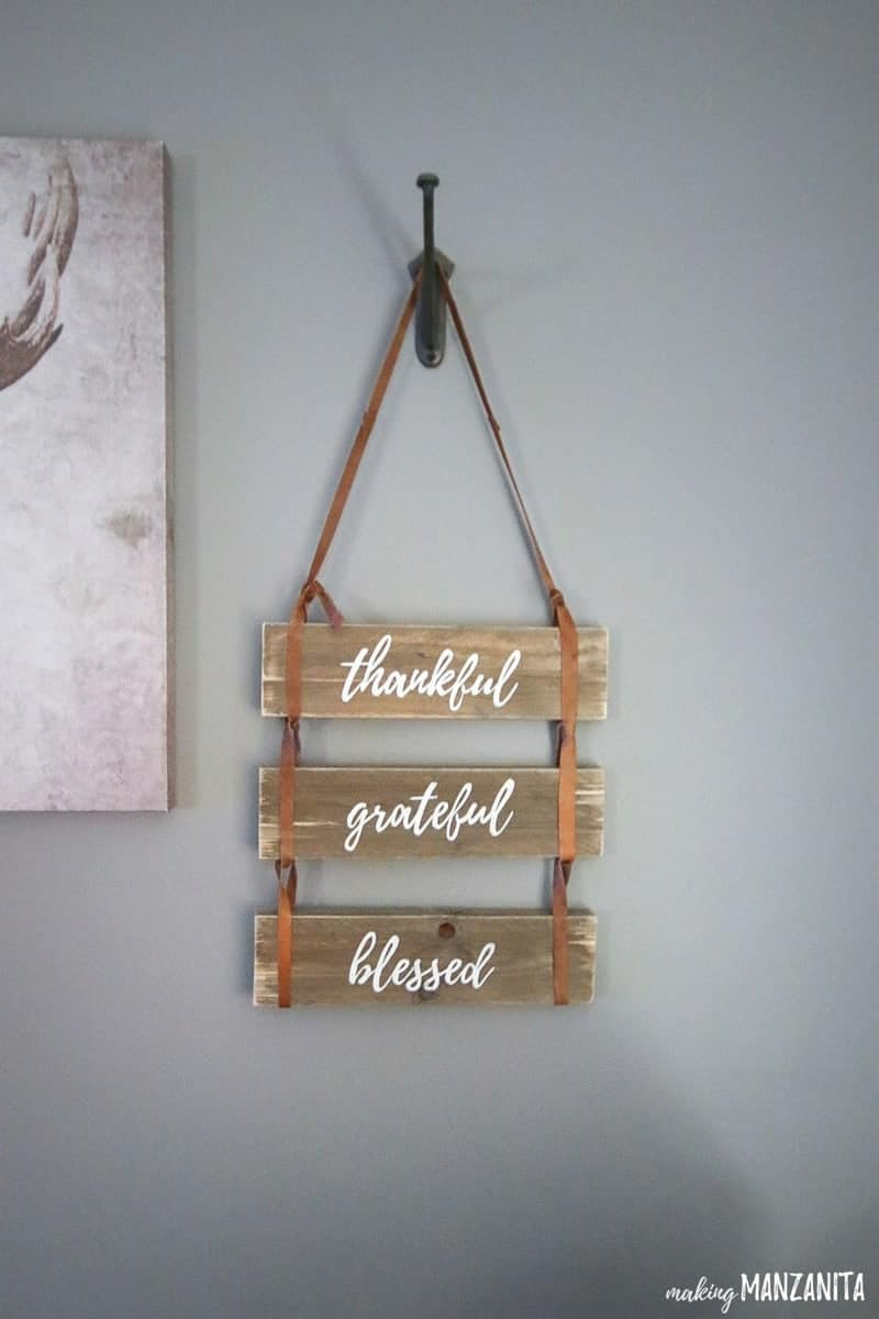 Leather sign with painted words that says thankful grateful blessed hanging on the gray painted wall