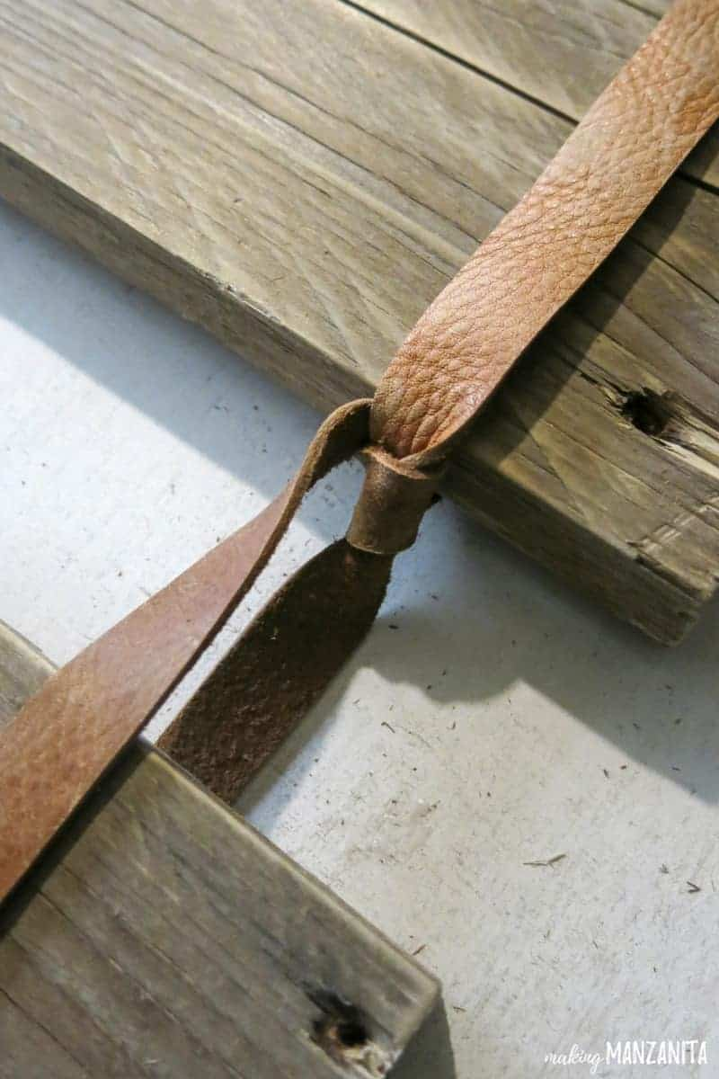 Leather strip knotted to hold the pallet board up on the sign
