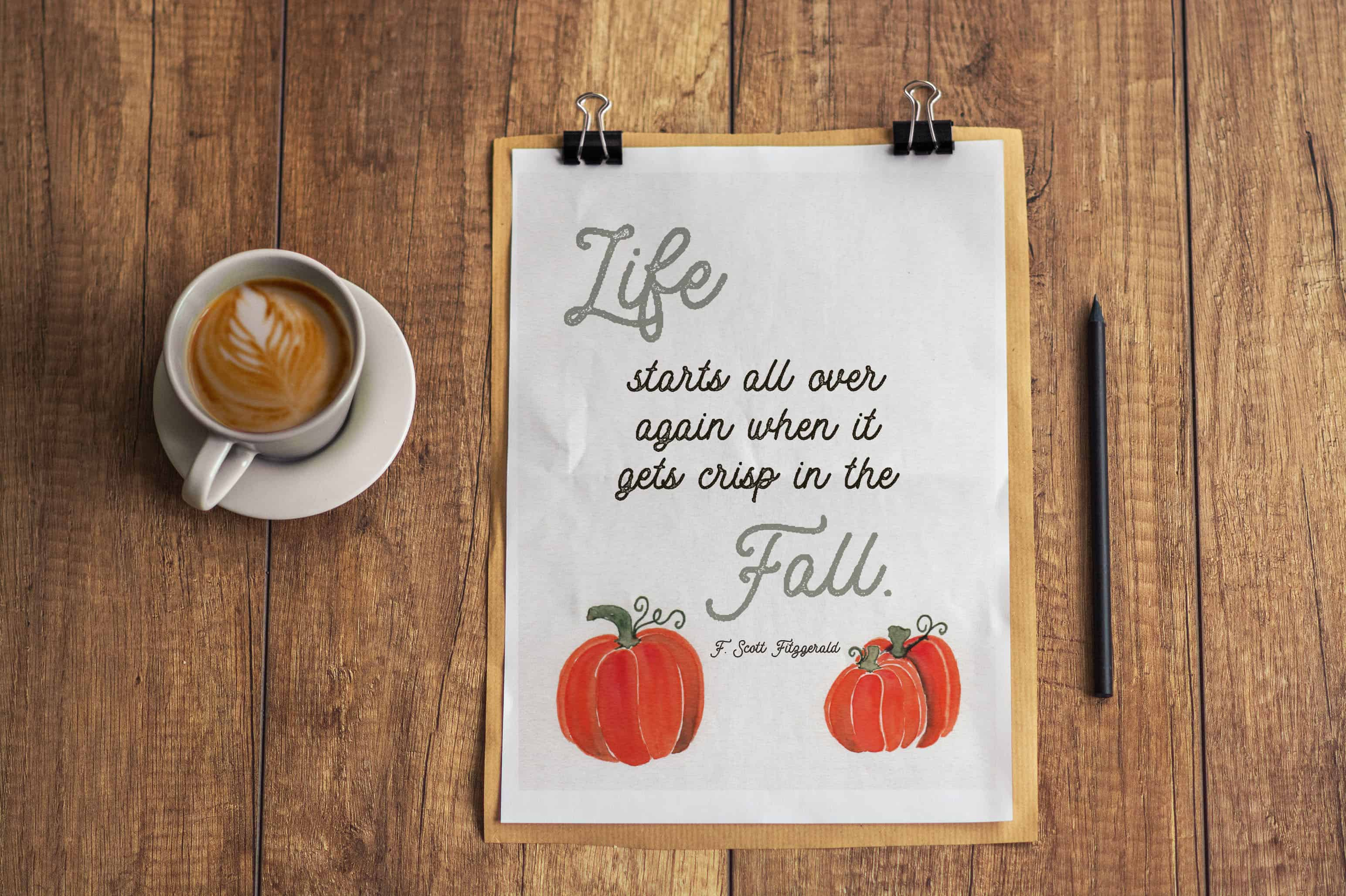 Photo of fall quote on paper laying on table next to cup of coffee. Paper has fall quote that says life starts all over again when it gets crisp in the Fall. F. Scott Fitzgerald.
