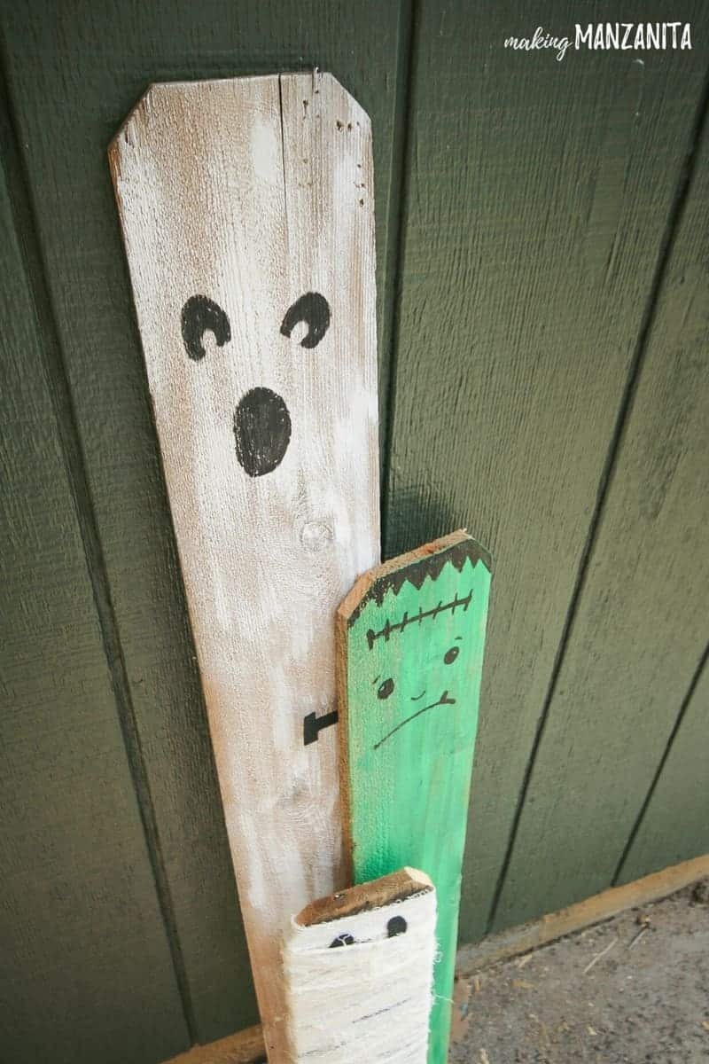 Ghost, Frankenstein and Mummy made from repurposed fence boards! Such a cute and simple way to create cheap Halloween porch decorations. | Ideas to Decorate for Halloween | Budget-friendly Halloween Decor | Halloween DIYs | Halloween decorations made from recycled materials