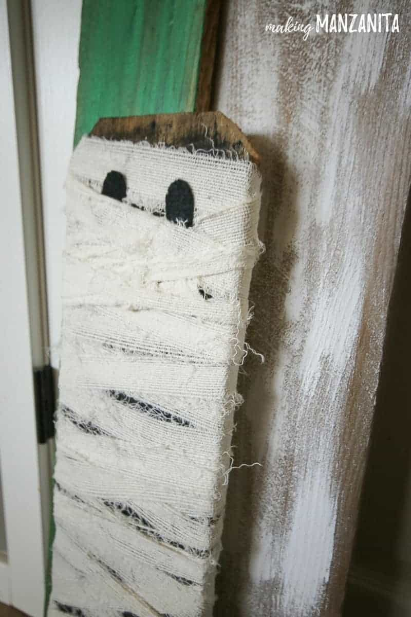 The most adorable little mummy decoration made from repurposed fence boards and white ripped fabric.