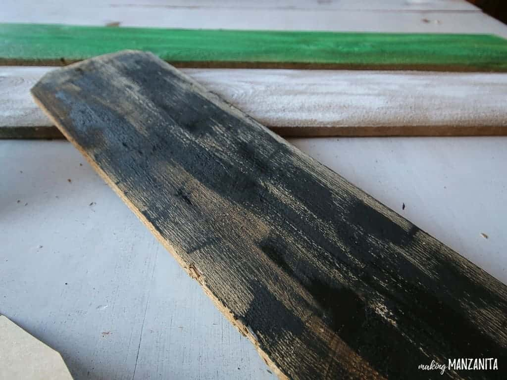 Paint an old reclaimed wood board black and transform it into a mummy Halloween decoration for your front porch.