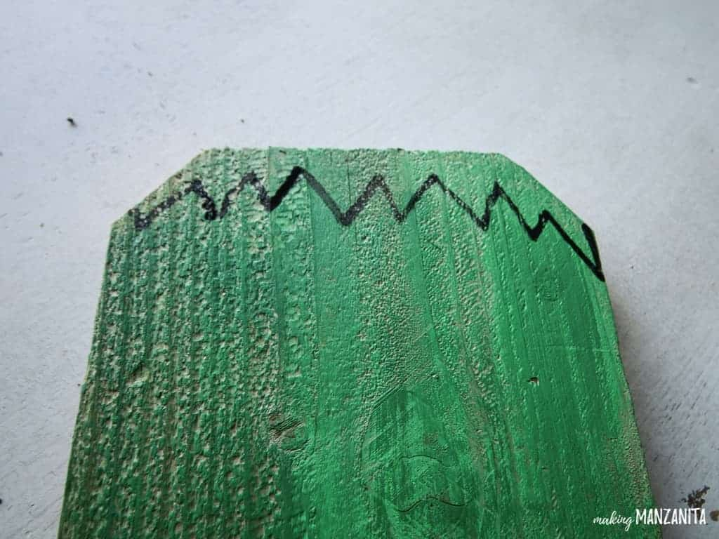 Use a black paint pen to create Frankenstein's face on the repurposed fence board to create these insanely adorable and cheap Halloween porch decorations!