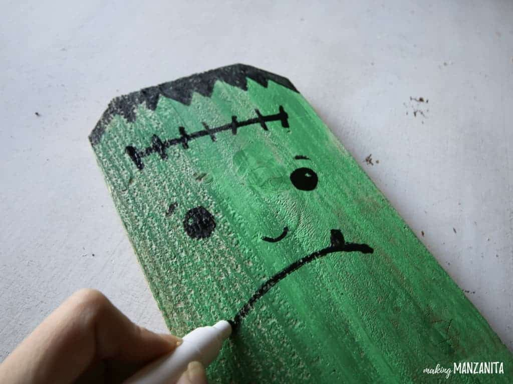 Frankenstein on fence board ! I love this idea for using repurposed fence boards to create Halloween porch decorations.