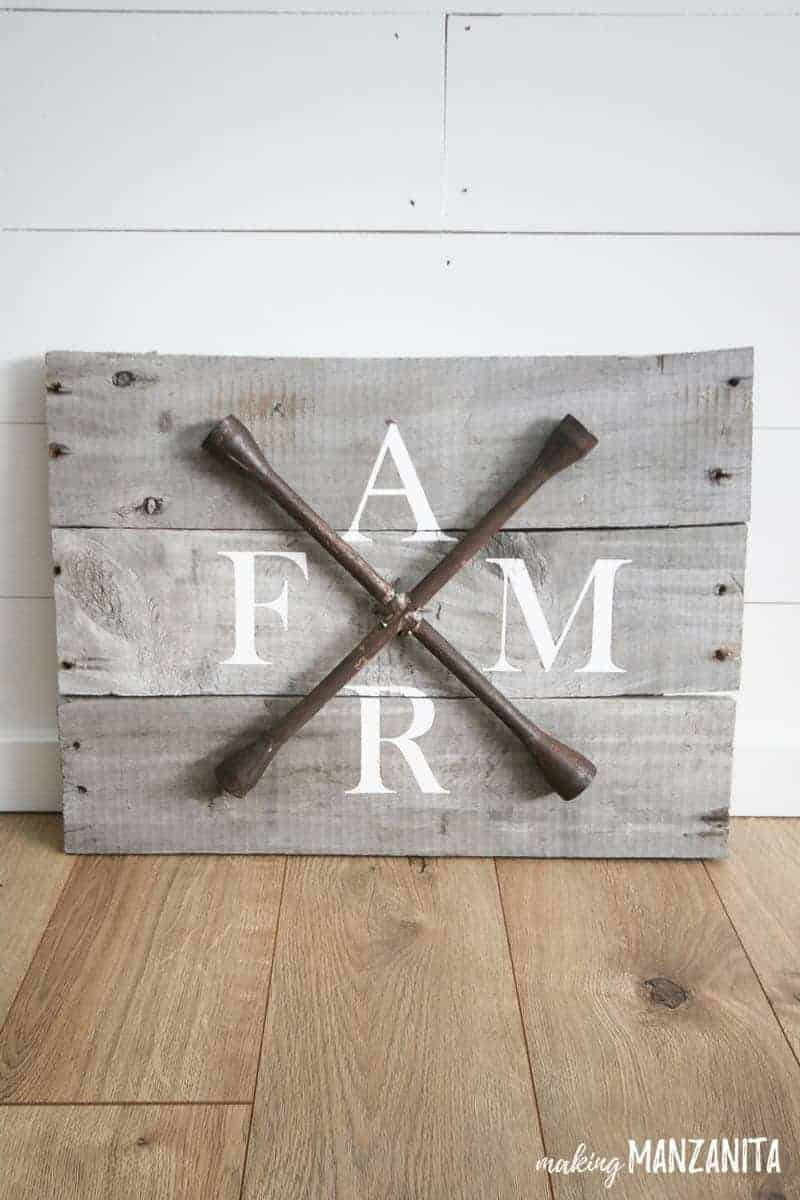 Farmhouse sign made with lug wrench standing against shiplap wall