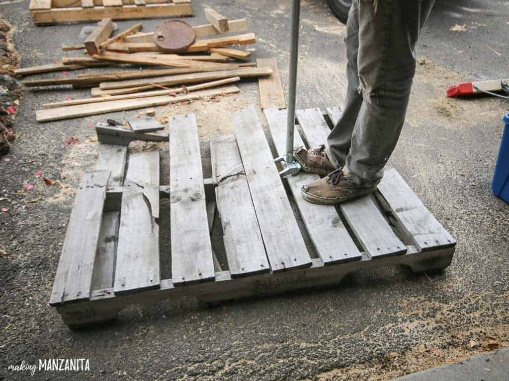 Man taking pallet apart with a pallet pry bar