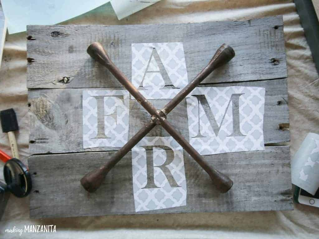 Farmhouse sign made with pallet wood and stencil with FARM letters around lug wrench