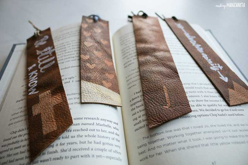 shows a few different bookmarks made from leather laying on a book