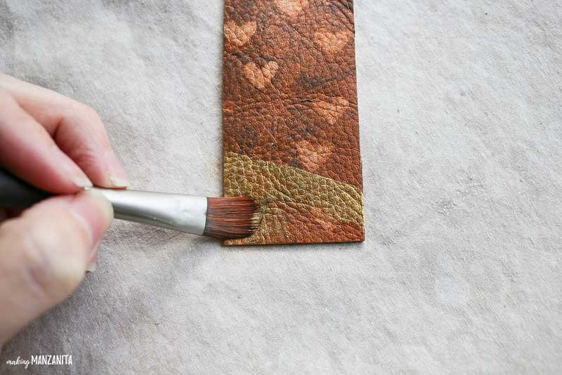 shows a dark leather bookmark with hearts that is being painted gold at the bottom