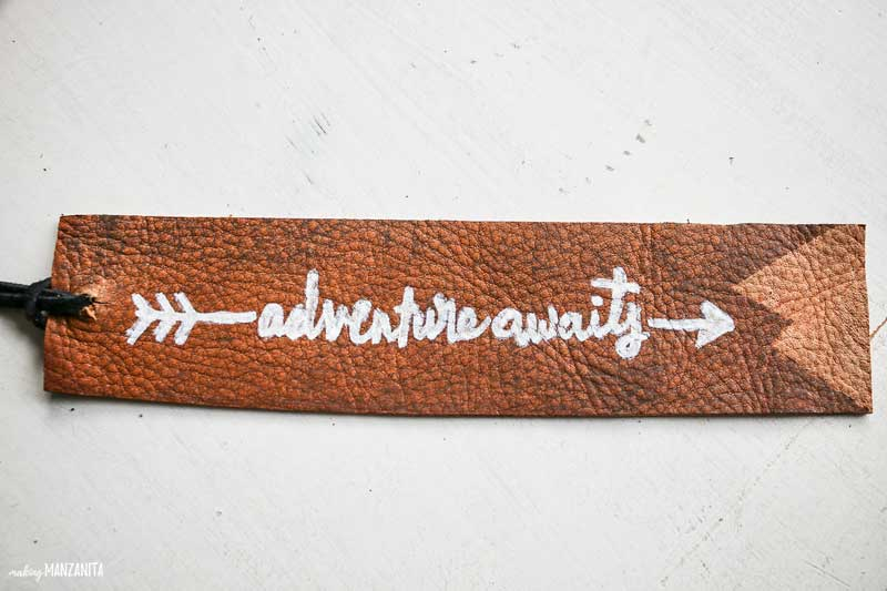 shows a leather bookmark with adventure awaits written on it