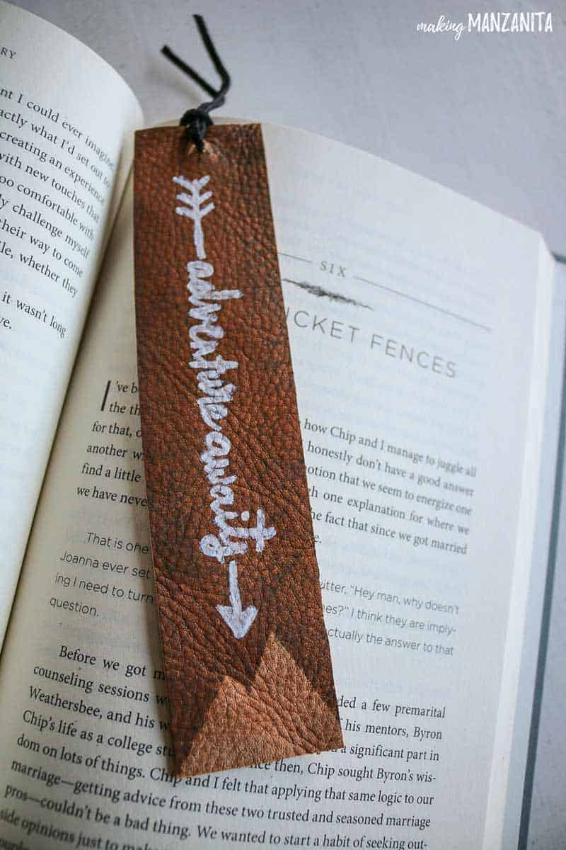 leather bookmark with Adventure awaits leather bookmark with mountains on it laying on an open book