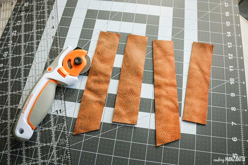 shows a few leather pieces on a cutting mat table next to a rotary cutter