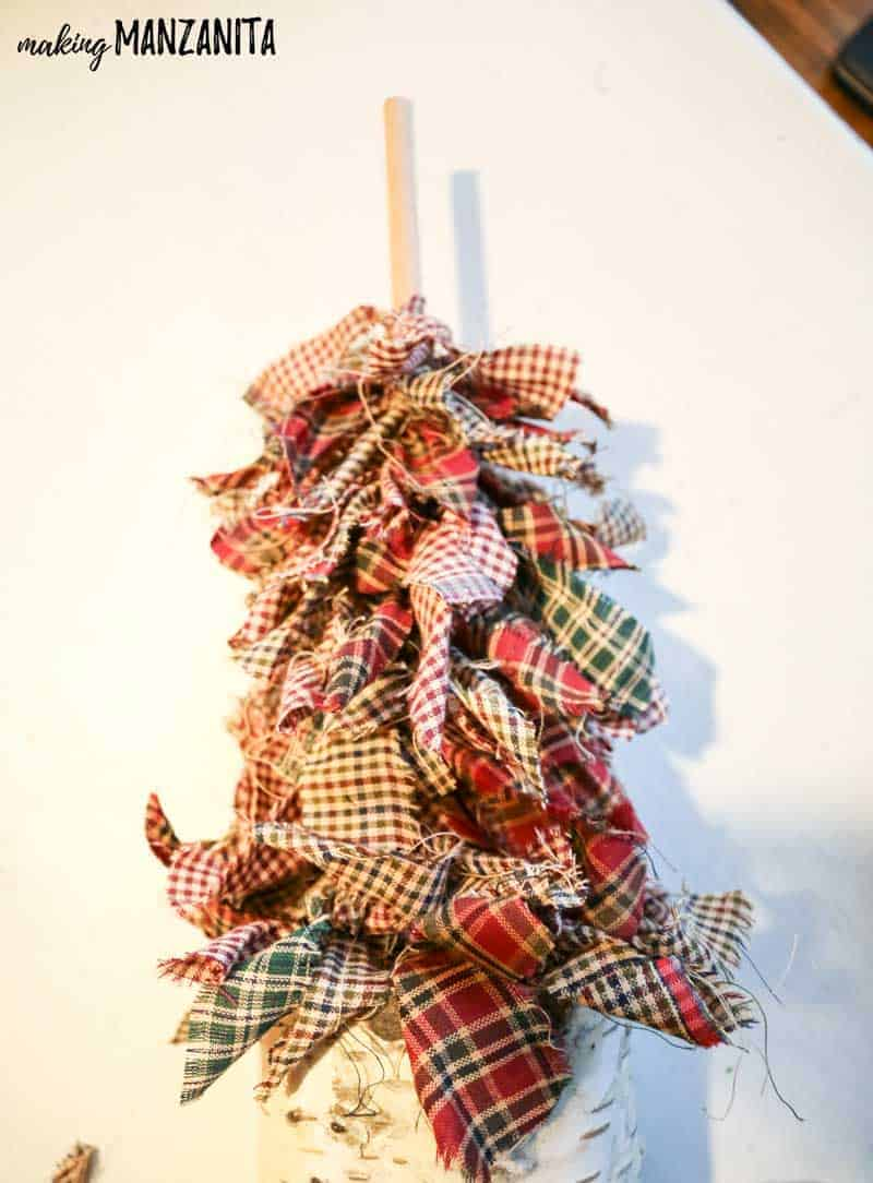 She ties a bunch of fabric scraps to a wooden dowel in a wood pillar....the result - rustic Christmas decorations! Click for a full tutorial!