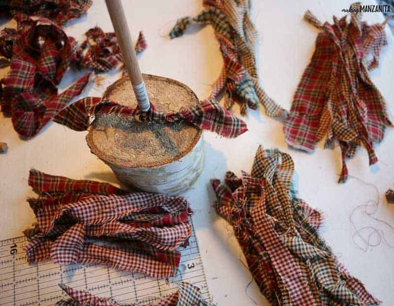 Homespun fabric strips and one strip tied to the wooden dowel for the fabric christmas tree