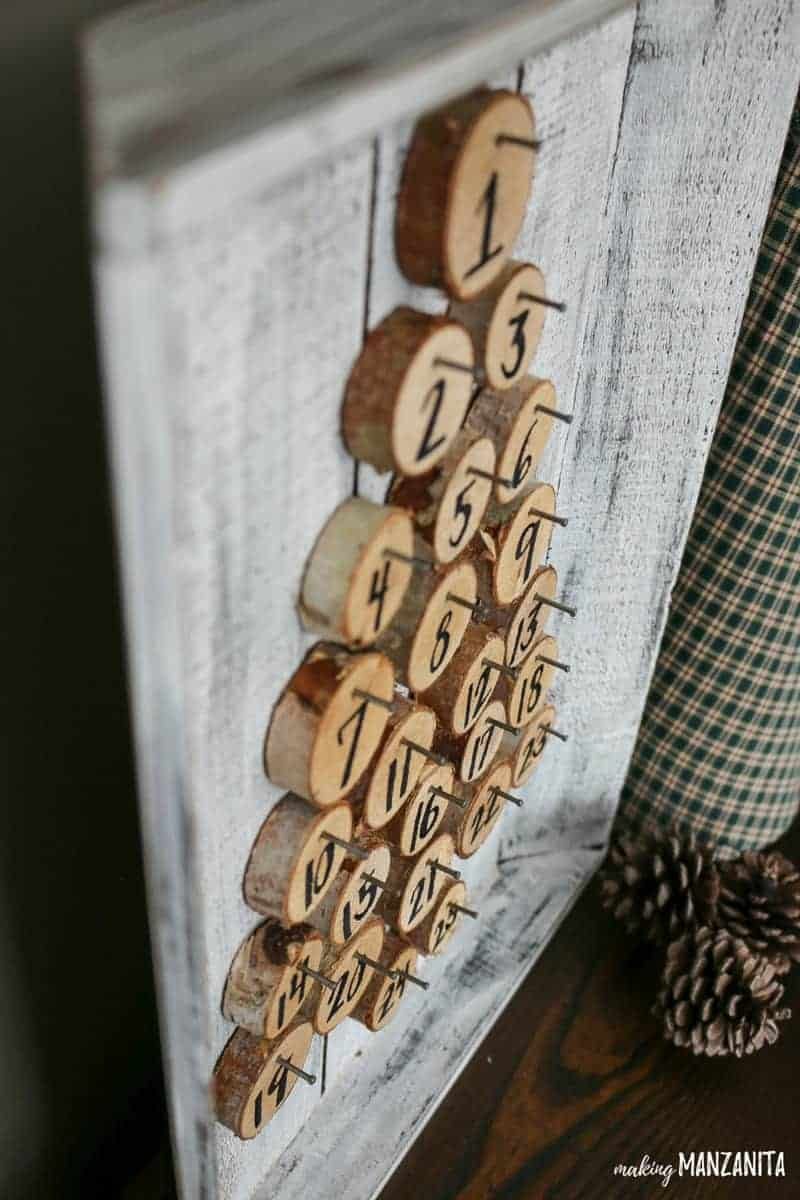 Nail birch wood rounds to a farmhouse painted wood tray for a unique Christmas advent countdown! I love this simple DIY for Christmas. Great way to countdown the days until Christmas.