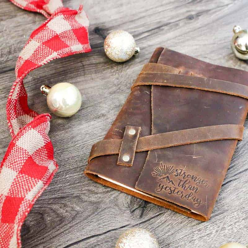 Leather wrap journal with quote engraged in corner that says stronger than yesterday on wood background with gold mini Christmas ornaments and red plaid ribbon laying next to it