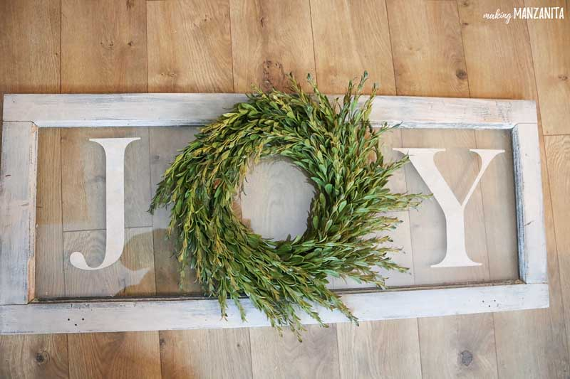 If you're looking for an easy to make Christmas DIY, you're in luck. This DIY joy sign with wreath on vintage window couldn't be more simple! Learn how to make this farmhouse Christmas sign to decorate your home for the Holidays.