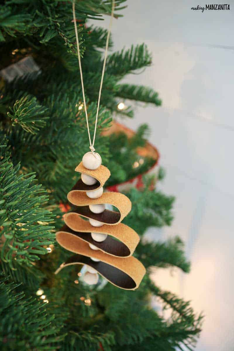 Scandinavian leather ornament with wood beads hanging on a green pine christmas tree