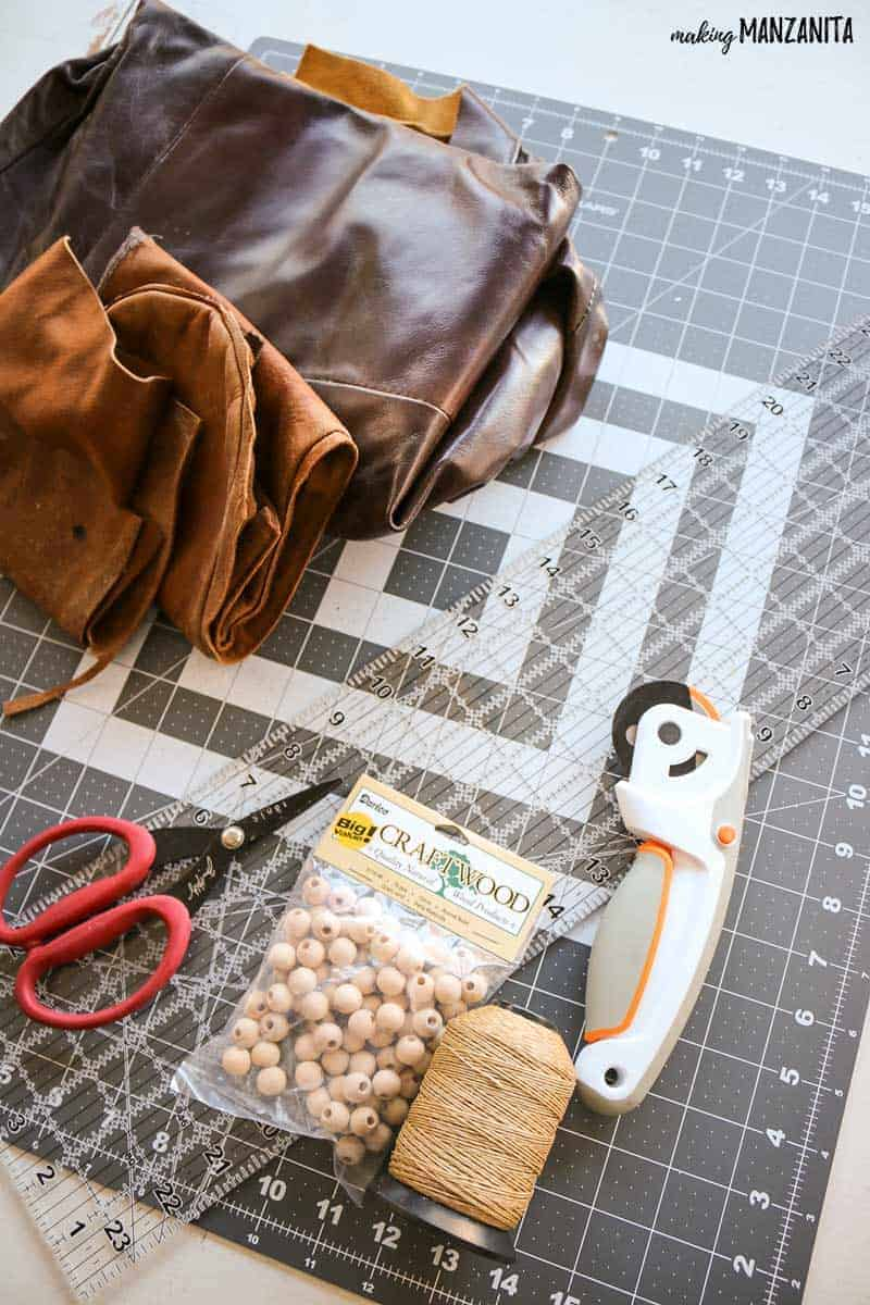 Craft supplies like rotary cutter, acrylic ruler, cutting mat, scissors, wood beads and leather flat lay on table