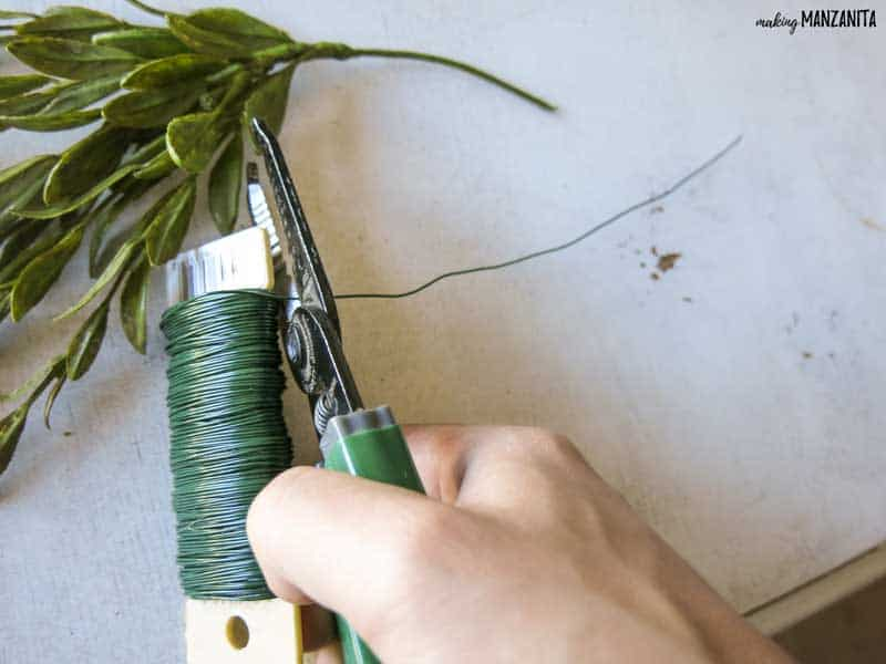 Hand clipping piece of floral wire with faux greenery in the background.