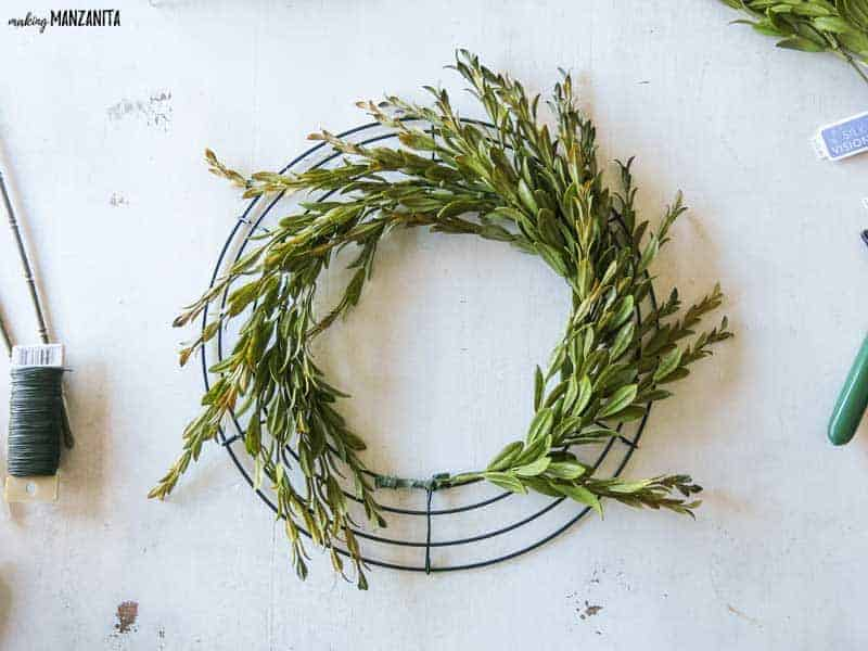 Wire wreath form laying flat on table with greenery attached to the inner ring.