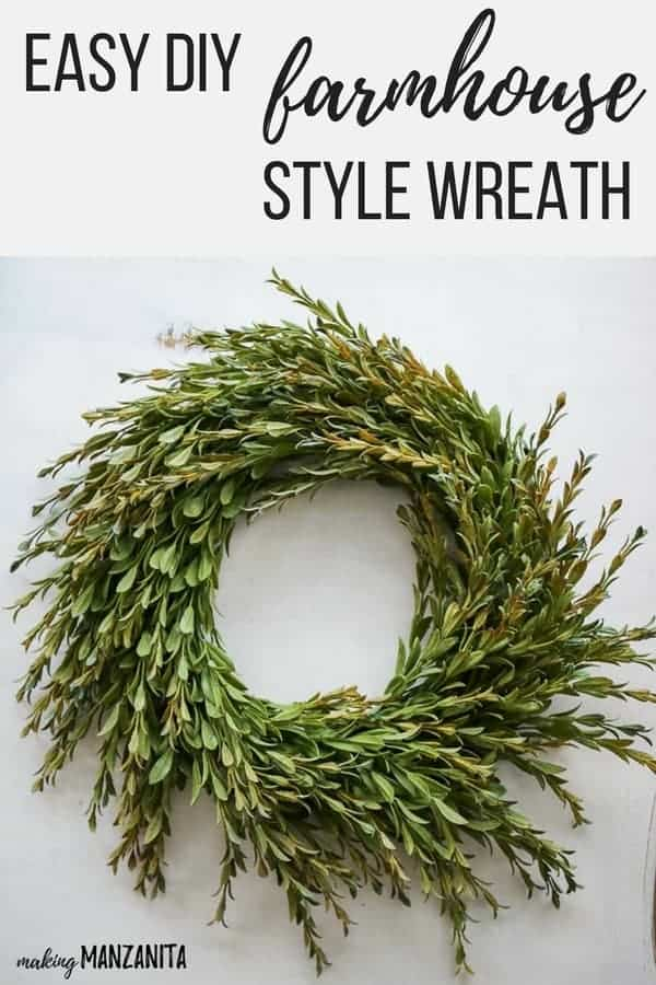 Farmhouse wreath with faux greenery laying flat on table with text overlay that says easy DIY farmhouse style wreath