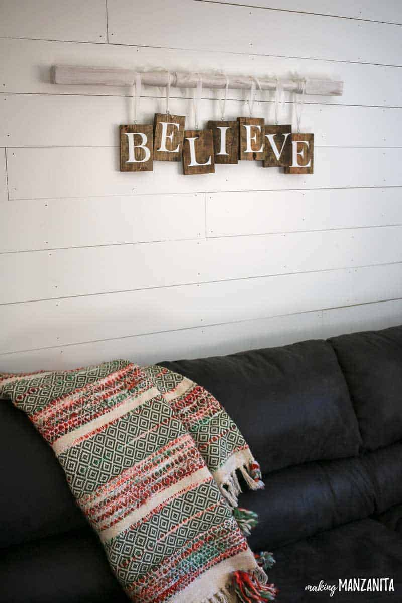 DIY Farmhouse Christmas sign | Bring out your inner Joanna Gaines | Christmas sign above couch in farmhouse living room | Christmas home decor ideas | Christmas wood sign | Spindle on wall with letters hanging from it | Simple Believe Holiday sign
