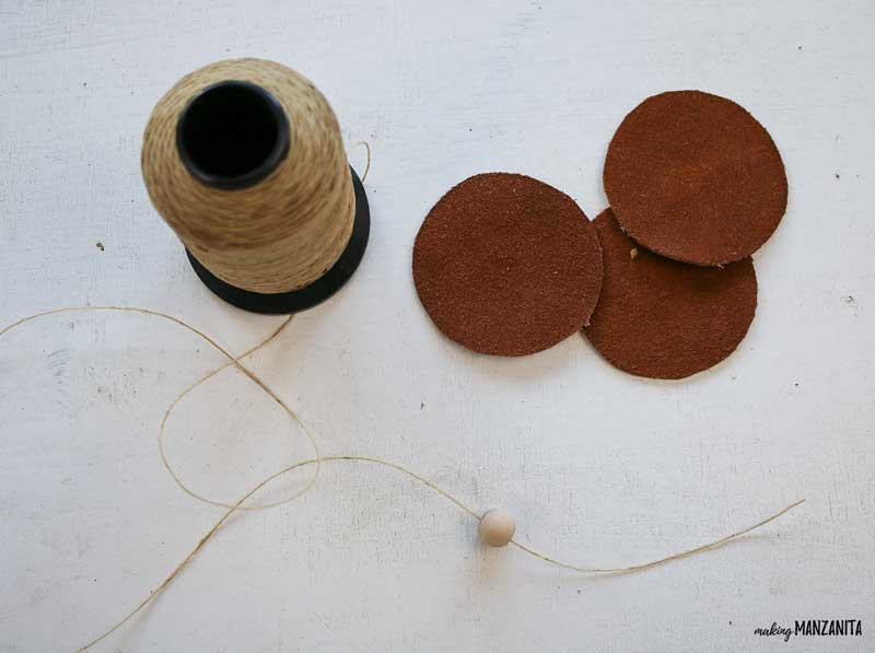 Start stringing wood beads onto twine for your DIY leather Christmas ornaments