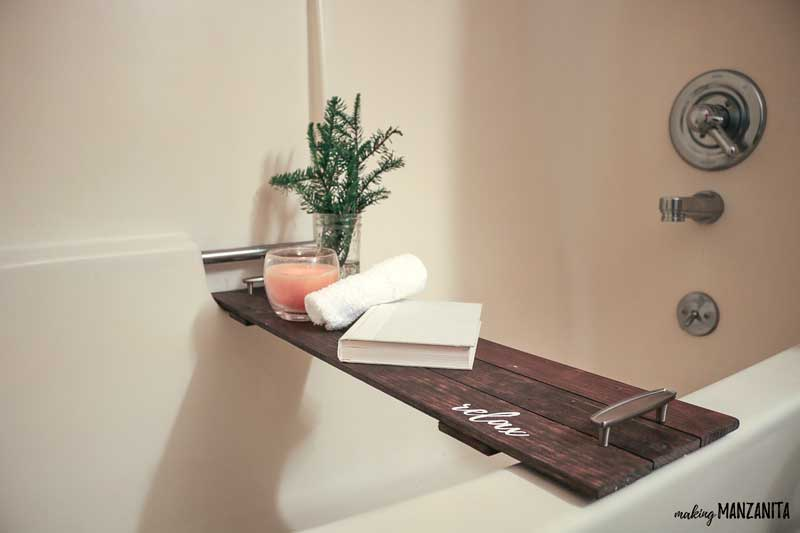 Dark wood bath tray with modern farmhouse style sitting in bathtub with greenery, candle, towel and book