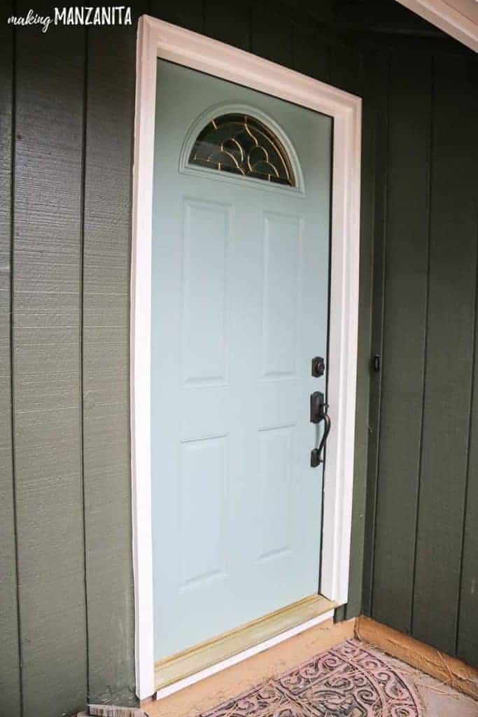Light green painted with In The Moment by Behr Paint front door with white trim and hunter green paint on exterior siding