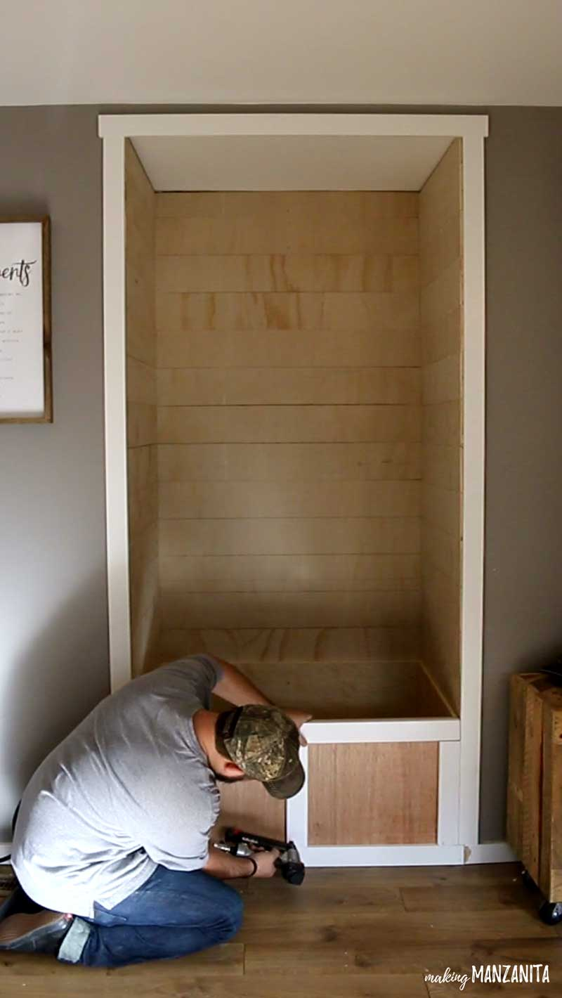 shows a face on view of shiplap alcove with a man nailing on trim  to the plywood base reading nook bench with white trim and gray walls