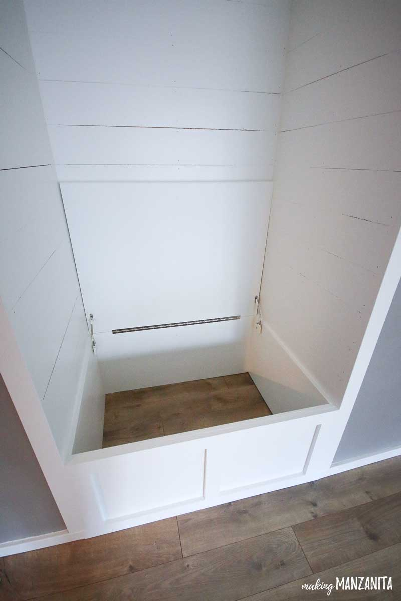 shows the white shiplap reading nook with top plywood lid or seat screwed into the piano hinge that is connected to box at base of the built in reading nook bench