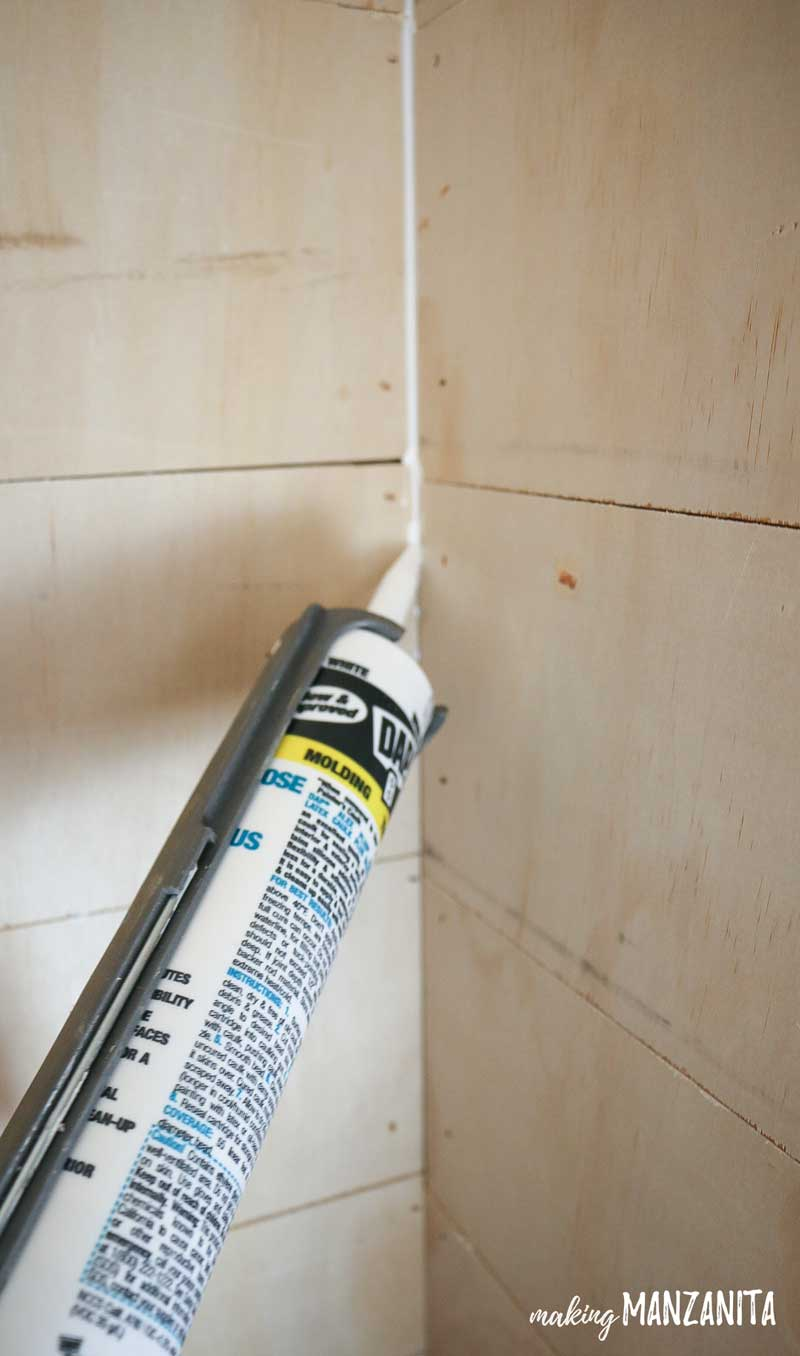 shows someone using caulk in the corner of the plywood shiplap in living room alcove