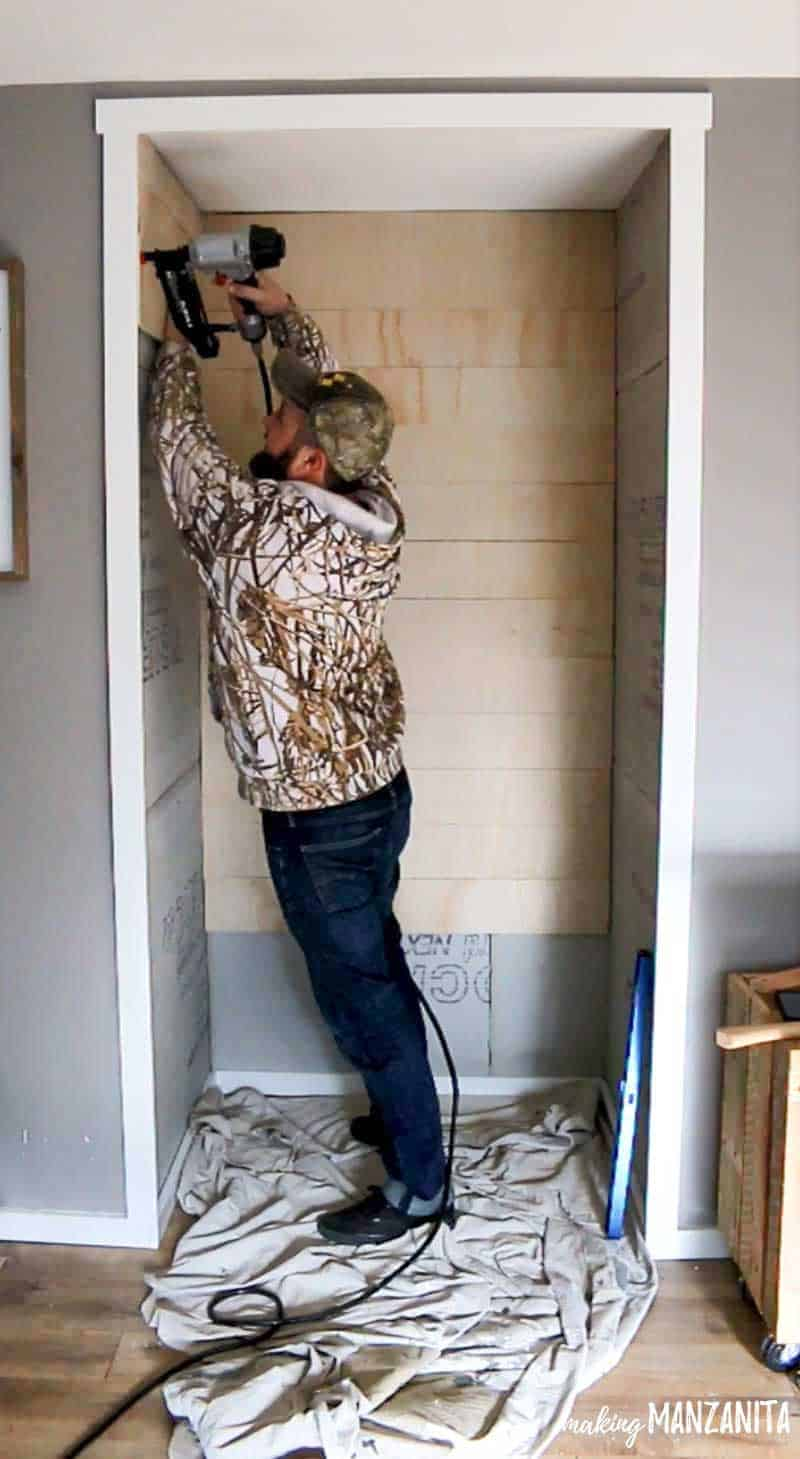 shows a man nailing shiplap on to the wall into the alcove