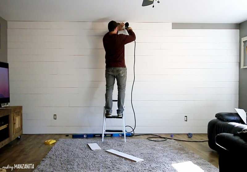 a man on a small step ladder putting up the top row of shiplap on a wall