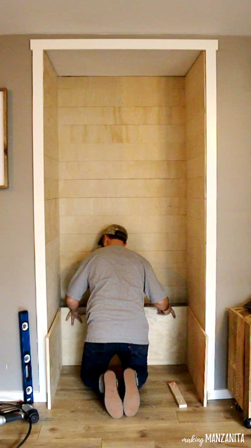 shows a man finishing putting in shiplap on the walls in the alcove and putting in plywood for the base storage bench of the nook