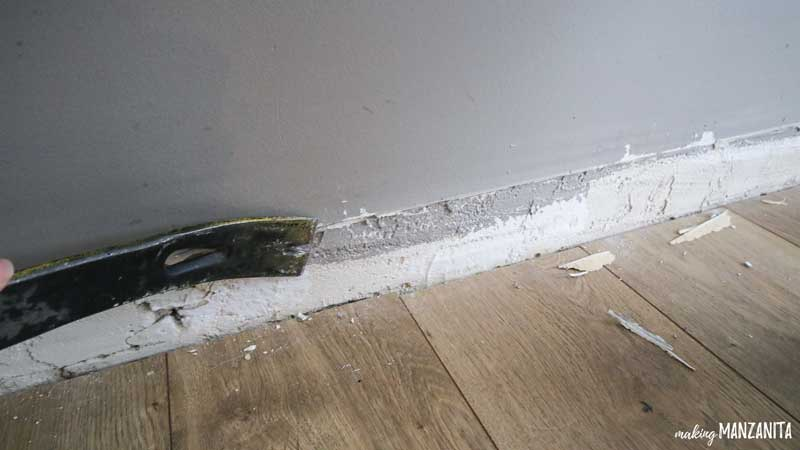 close up of a crowbar scraping down where a baseboard used to be