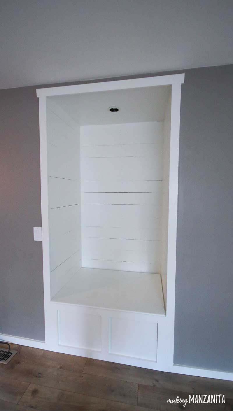 See how this awkward alcove is transformed into a farmhouse style DIY reading nook with storage!! This shiplap wrapped nook with seating will make you want to cozy up and read a good book.
