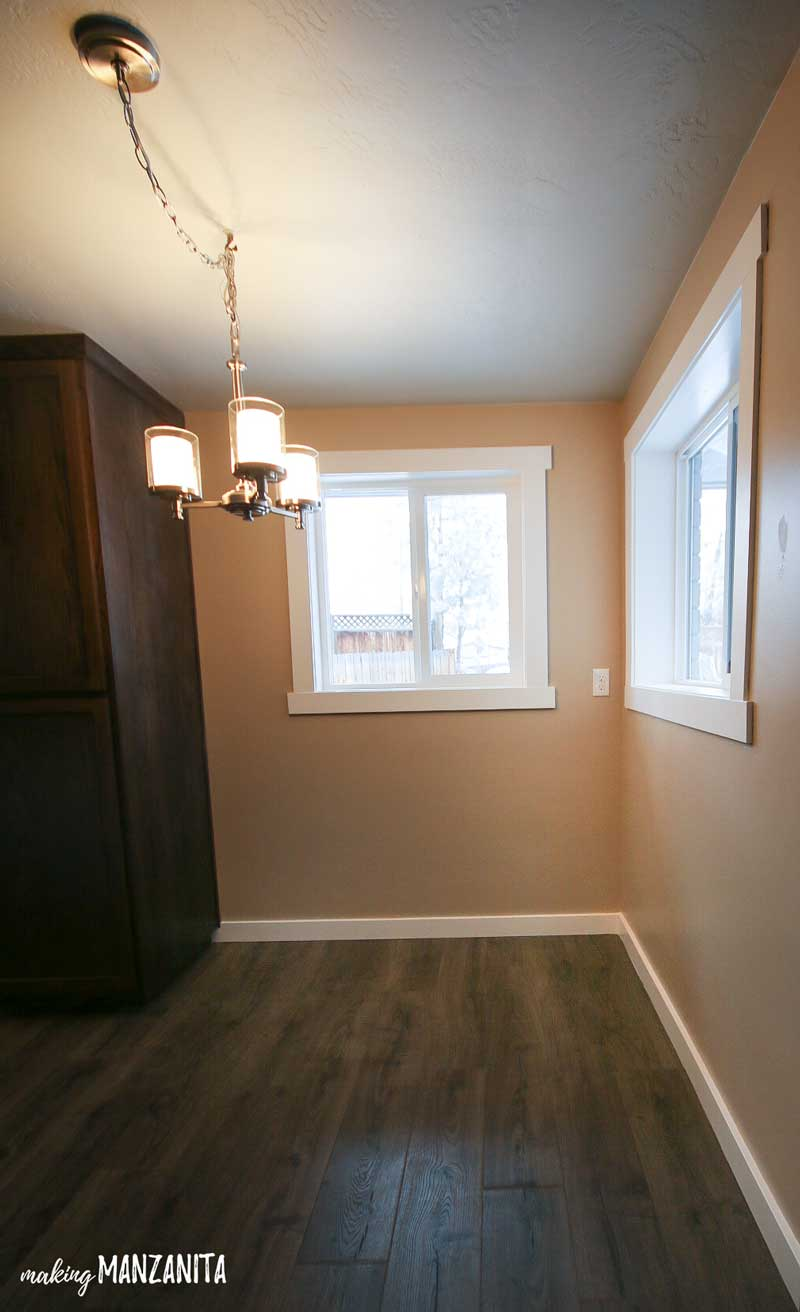 Corner breakfast nook area in kitchen with tan walls and white trim with windows and hanging light