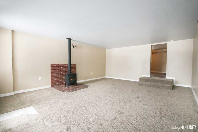 Empty living room tan walls and brown carpet with a black freestanding fireplace and brick surround and two stairs before the renovation