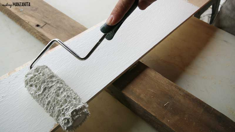 photo of a paint roller applying white paint to a 2 by 4 board