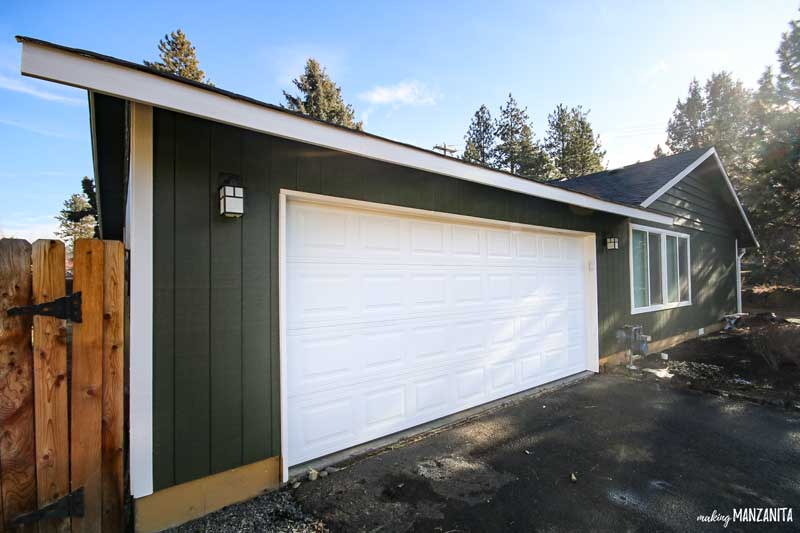 Bright white garage door on green house. Green color is Black Bamboo by Behr.