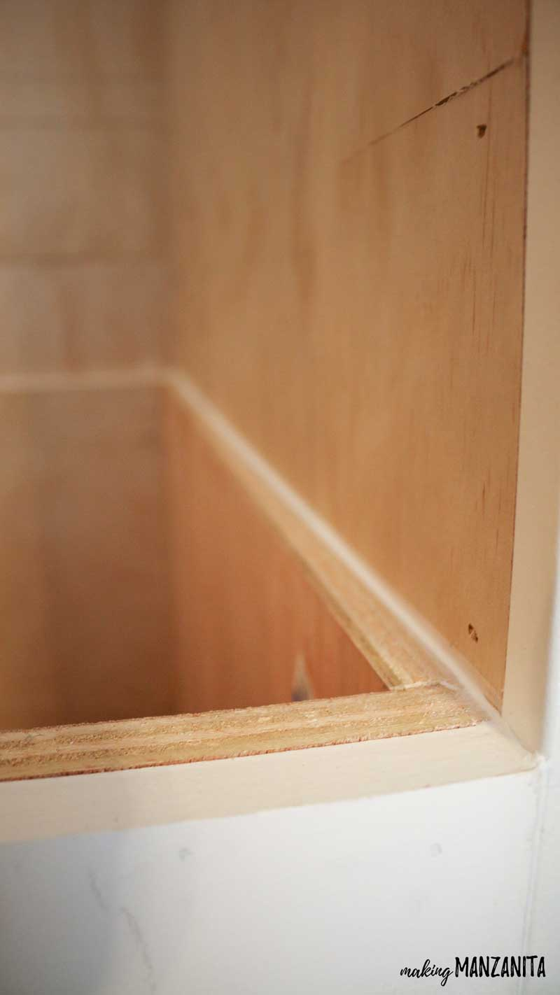 shows the top part of the plywood reading nook bench that has been caulked and scraped