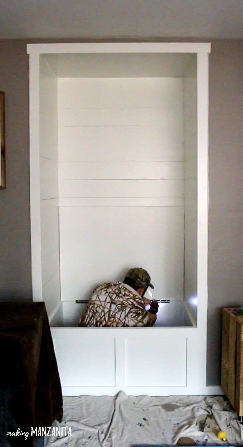shows a man screwing in a piano hinge to the white plywood bench at the base of the shiplap built in reading nook with white frame and gray walls