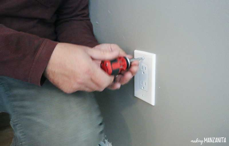 photo demonstrating the removal of a wall outlet cover