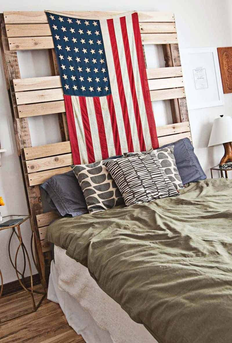 Casual looking bedroom with wood pallet headboard, vintage flag hanging as over the bed decor, olive green bedding