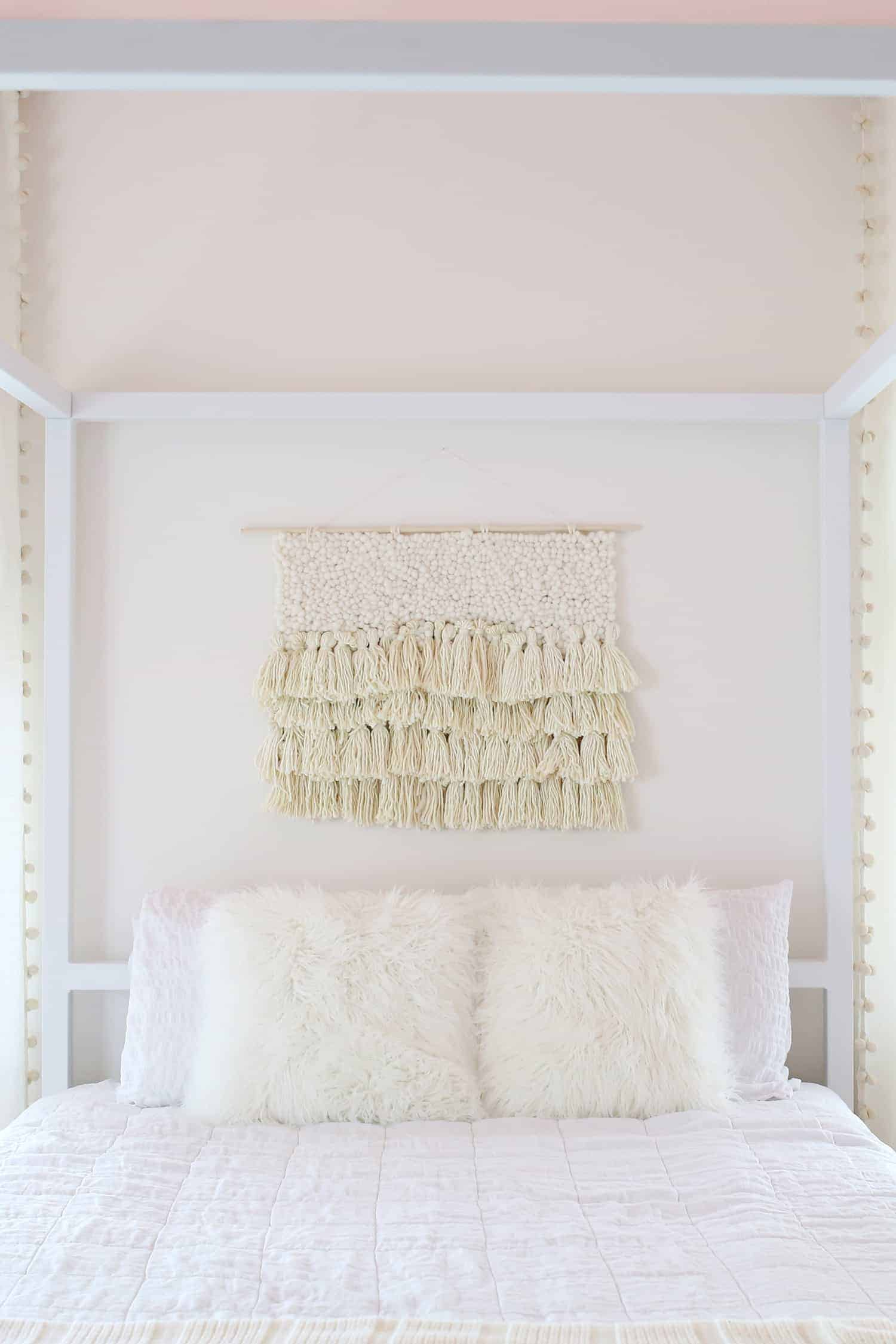 White bedroom with white bedding, fur pillows, white bedroom and a cream colored boho wall hanging for above bed decor