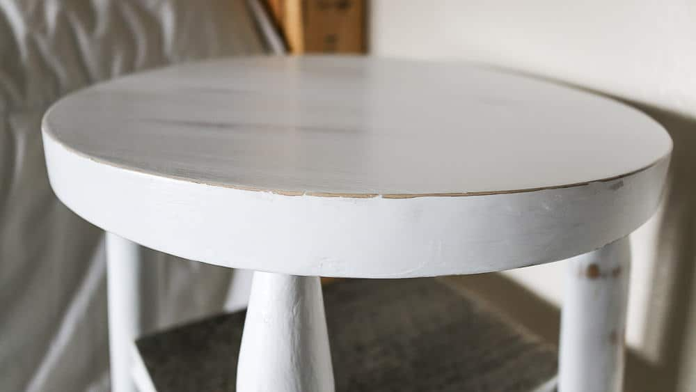 close up of a stool seat painted white, with small chips in the paint around the rim