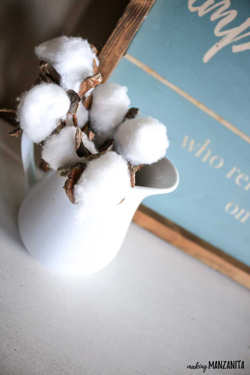 White pitcher with faux cotton stems sitting on table in front of blue farmhouse sign
